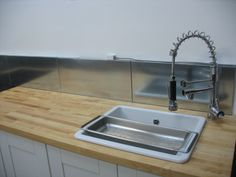 this backsplash was made from metal ikea shelves. they look cool, though i'll bet they rust in a new york minute :(