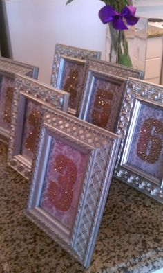 DIY Custom Table Numbers. I love the sparkle and scrap book paper for the background. Cute and affordable.
