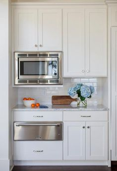 Wonderful kitchen features upper cabinets fitted with a microwave and lower cabinets fitted with a Thermador warming drawer paired with a white marble countertop and a white subway tile backsplash finished with white grout.