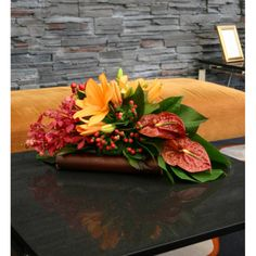 tropical green foliage, red vanda orchids, tiger lillies, chocolate anthuriums and hypericum