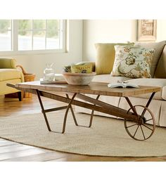 """Distressed Wood Wheelbarrow Coffee Table. Crafted of rough-hewn wood and cast iron, with an authentic-looking wheel and distressed finish. Heavy-weight table, generously sized to make a statement. 68""""L x 27-1/2""""W x 19-1/4""""H"""