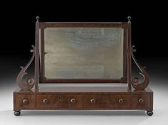 """Regency Mahogany Shaving Stand, first quarter 19th century, the period rectilinear mirror plate in a molded frame supported by scroll and post brackets on a base with a band of drawers, h. 21"""", w. 30"""", d. 8""""."""