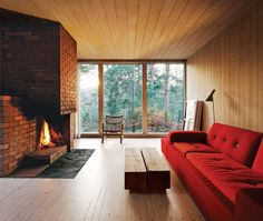Optimal lounging happens within close proximity of a cozy fireplace. The interiors of this Swedish cabin are clad in white-glazed pine, a contrast to the black-stained facade. The brick fireplace is original. Near a Polder sofa by Hella Jongerius for Vitra is a vintage rocking chair that came with the house. Photo by Ivan Brodey. Photo by: Ivan BrodeyCourtesy of: Ivan Brodey