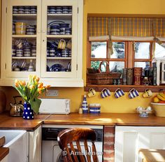 Ambience Images | Collection of blue and white Cornishware in glass-fronted cream cupboard beside window in yellow cottage kitchen