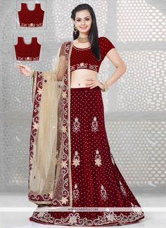You will be the center of attention in this attire. Be the sunshine of everyone's eyes dressed in this beautiful maroon velvet and net a line lehenga choli. The lovely embroidered and resham work th...
