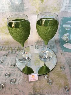A set of 2 glittered wine glasses in either of the 2 colour choices offered perfect any occasion  Cadbury purple Lime green  I like to leave the rim clear of glitter or decorative detail to allow the user to drink comfortably from the glass. They each come with care instructions as they are hand wash only and dont take kindly to being submerged in water for long periods of time   If you wish to purchase more than the amount available please contact as this can be arranged  Terms & conditi...