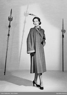 Modell i kappa, hatt med fjäderpenna, pärlhalsband, pumps och handskar. Spjut i bakgrunden. Fotograf: Sten Didrik Bellander, ca 1950-1955