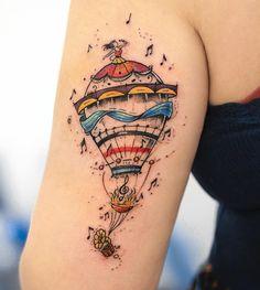 Tatuagem criada por Rob Carvalho de São Paulo.    Balão colorido e delicado com música ao redor.