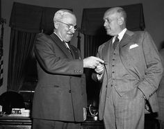 """Louis Johnson (March 1949 - Sept. 1950)  Defense Secretary Louis Johnson (right) gives new identification card to President Harry Truman at the White House on Nov. 9, 1949 in Washington, listing him as commander in chief for an """"indefinite"""" term. (Source: Department of"""