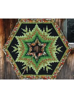 """Use bargello panels to create this intricate design that will add a delightful accent to your Christmas tree. Intermediate quilters will test their skills with this beautiful pattern. Finished size is 64"""" diameter."""