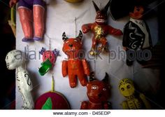 Paper mache dolls representing red devils and skeletons sit for sale in a Mexican folk-art workshop. - Stock Photo
