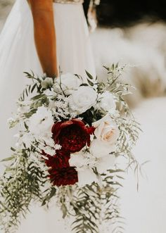 Red + cream bridal bouquet with delicate greenery   Image by By Amy Lynn Photography