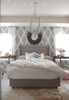 Diamond stenciled wall, fluffy layered rugs, grey tufted bed, cool chandelier