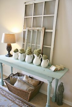 Console table with windows propped above; practical basket storage on shelf below. Cute! I esp. like the table...add some turquoise to make it pop!