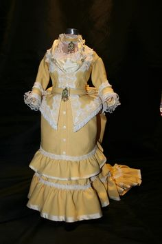 This is a half-scale dress I made based on a pattern from Janet Arnold and a painting of a member of the Russian Czars' family.  It is made of a yellow silk file and white lace.  It was made for a show of Half-scale clothing I did in Macon, Mo and it includes all of the foundation and support garments (corset, collapsable bustle, 2 petticoats and a chemise.  The entire piece stands less than 3 feet tall. Designed, patterned, cut and sewn by Costume Designer Jack A. Smith