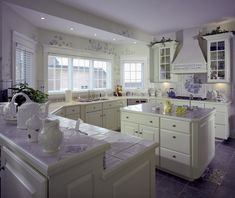 This white kitchen is enlivened by a smattering of purple throughout: purple tile flooring, countertops, and floral backsplash unify the space.