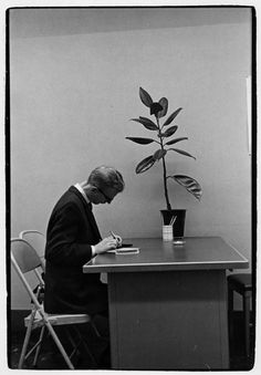 Man writing at table next to plant.. From Duke Digital Collections. Collection: William Gedney Photographs and Writings. Dust in print. Mark: None. Date of print: Unknown.