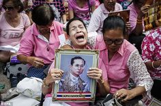 Many of those outside the hospital clutched pictures of the King and wore pink and yellow shirts