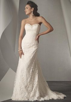 Draped all over lace strapless gown with a sweetheart neckline that has been accented with metallic embroidery, crystal beading, pearl, and rhinestones. The gown features a fit and flared silhouette, and is finished with a chapel length train.