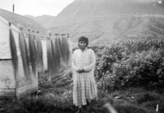 """""""Wassa (aka Maggie Prokopioff) standing next to drying bundles of Elymus, or wild rye grass, for use in making baskets - Aleut - 1936 {Note: The wild rye grass that's cut for making baskets, is cut when it's green, and the outer leaves are stripped off. Then many small bundles, such as the one's in the photo, are hung up on a line to dry. It is said that the drying of the wild rye grass is a long and slow process, taking sometimes up to eight months because of the damp air.}"""""""