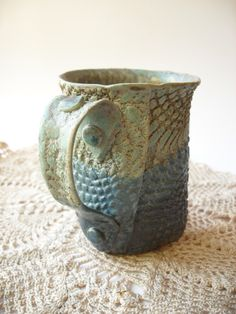 This quirky mug is glazed in turquoise and dark blue, which overlap to create a medium blue. The inside is speckled yellow-brown, and there is a