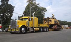 Very nice Peterbilt TriAxle and the CAT track machine totally disassembled....on a 4 axle beam trailer.