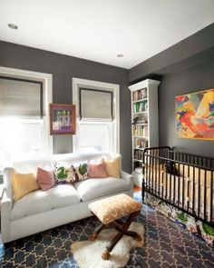 Sophisticated nursery ... touches of whimsical fabric and the moorish rug are perfect in this stylish nursery. Looks as though it can go from infant to teenager in a blink. (Although the comfy white couch may be short lived with kids!)