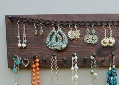This Handmade Jewelry Display Rack is crafted from reclaimed pine, given a dark walnut finish and completed with a clear, matte acrylic for long lasting durability. walnut finish. The nails come from Americas oldest nail manufacturer and are designed after the hand forged nails of the 1700s, giving the piece a clean but rustic feel. There are 2 nails on top and 17 on the bottom, providing ample space for all your necklace, ring and bracelet storing needs. A black metal chain has 29 links for…