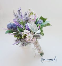 This silk wildflower bouquet has lilac, lavender, wildflowers, and lambs ear. Wrapped in burlap and lace with a twine overlay, this makes a