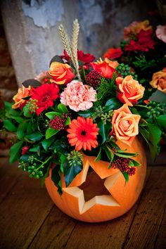 flowers in pumpkins carved with hearts & stars.