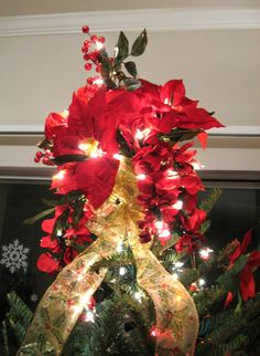 This is my home made Christmas tree topper! Lately I have found that most store tree toppers are awfully boring or ugly... so I came up this instead! I just used some wire to bundle together some wired lights, Poinsettias, and cranberry sprigs. I made a ribbon bow to go on its base and viola!