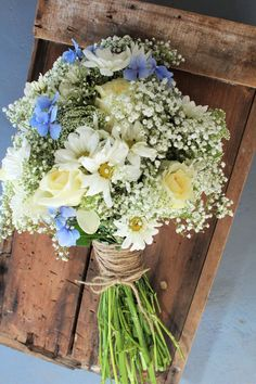 Wedding flowers on a budget! This blue and white bouquet was made for a summer wedding and used baby's breath, Queen Anne's Lace, Daisy, Cream Roses and hints of blue hydrangea.