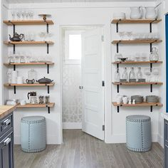 Storage space in small cottage kitchens fills up fast, so designer Paige Schnell installed open shelving along an empty wall. | Coastalliving.com