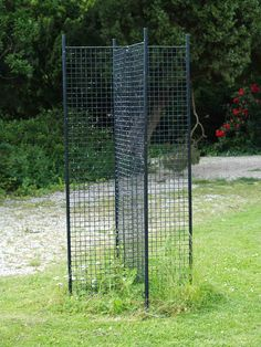 No place to grow climbing roses, check out this simple freestanding structure. It's simply two metal panes that form four separate growing areas. One rose is planted in each growing area for a total of four roses per structure. There are three other photos that relate to this one.