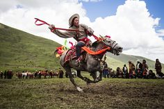 A horse rider makes his way across the makeshift racetrack near Litang. Image Credit: Marc Ressang