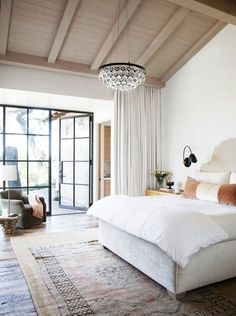 Hot rolled steel doors and windows, the only color is in the rug/scatter pillow. White walls, beams in the ceiling. Ochre lighting fixture. Nice mix of contemporary and traditional. via @domainehome