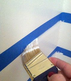 PERFECTLY CRISP PAINT LINES: Seal the edges of the painters tape with some of the base wall color & let it dry before painting on the contrasting color-- this way the paint that bleeds under the tape matches the wall & doesn't matter... GENIUS!