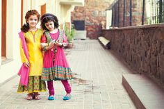 On the left - The jealous stares won't be just from the kids. She will be sitting pretty in this long ochre chanderi kurta with a contrast green floral it embroidery. Teamed with a printed inner and yellow knit churidar and she will be the star you know she is.   On the right - The new Bollywood starlet is here. The pink net anarkali comes with a colourful embroidered jacket that has cute tassels. Worn with a pink knit churidar and her red carpet awaits.
