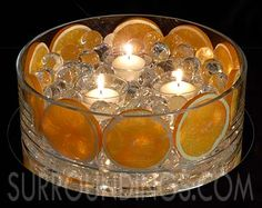 Fruit slices --- yellow lemons --- in water pearls & candles centerpiece.