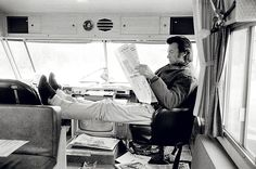 "Jaeger-LeCoultre's ""The Art of Behind the Scenes"" - Actor Clint Eastwood reads a newspaper in a mobile home between takes of ""Joe Kidd,"" a Western directed by John Sturges. 1972 