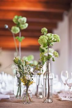 Cape Town Wedding:  Single stem greens in mix and match bottles. Wedding reception decor. Green White Rustic South African Wedding // Justin Davis Photography