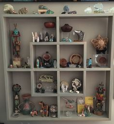 Shelf cubby unit on wall of same color with collection of fetishes, pottery, basketry and more!