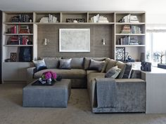 Family room sofa recessed between book shelves. Charcoal grasscloth by Donghia lines the alcove, and the custom sectional by Furniture Masters in grey velvet.