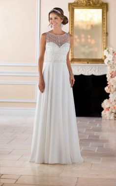 From Stella York, this beaded high neck wedding dress is a fresh, fashion forward bridal look with a timeless twist. Capri chiffon over Lavish satin in a casual column silhouette with an ornately beaded neckline is both comfortable and stylish. The scroll pattern in the bead work helps to highlight and define the waist, while the chiffon skirt is breezy and cool-perfect for a wedding beach or an outdoor venue! The beading continues on the open back, while the skirt leads into a modest train…