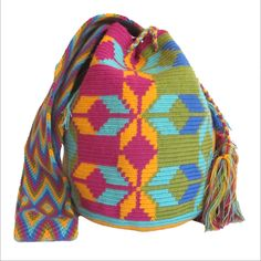 $90.00. Tacho Bag. About Wayuu Mochilas: These crochet Wayuu bags are made by Wayuu women and designed by Lombia & Co. The colors of the mochilas Wayuu are inspired by the vivid colors that surround region of La Guajira. Sand, sea, desert, sun and a clear sky are constants in the landscape. Geometric figures are a signature of these mochila bags.