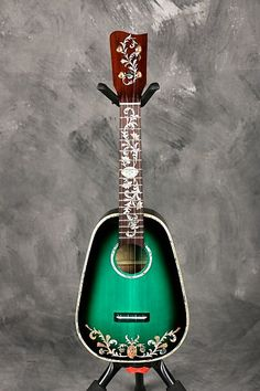 This is a one of a kind custom made soprano ukulele with inlays unlike anything I've ever seen. It has to be seen to be believed! Its a gorgeous green sunburst in a pineapple shape with banjo style peg tuners. It has spectacular mother-of-pearl inlays on the headstock, fretboard, top, and back, a...