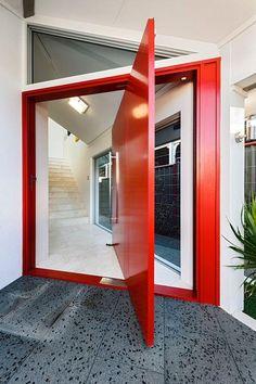 Charmosa porta pivotante vermelha, um brilho para a entrada da casa.  Fotografia: http://www.decorfacil.com/portas-pivotantes/