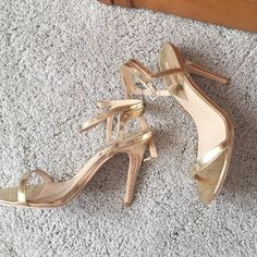 NEVER BEEN WORN gold stilettos I bought these adorable heels for prom last year and didnt end up wearing them because they would have made my dress too short. These are so cute with an ankle strap and the gold color makes them super fun and festive Forever 21 Shoes Heels