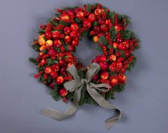 Paul Thomas Christmas wreath with crab apples in various sizes on a classic blue pine base with clusters of bright red Ilex berries, finished with a black and cream'humbug' bow