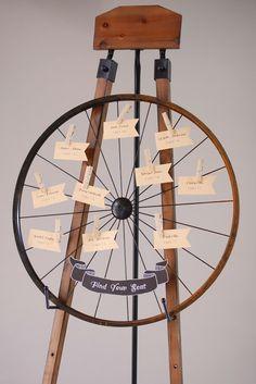 Rustic escort card display on an old fashioned wagon wheel.